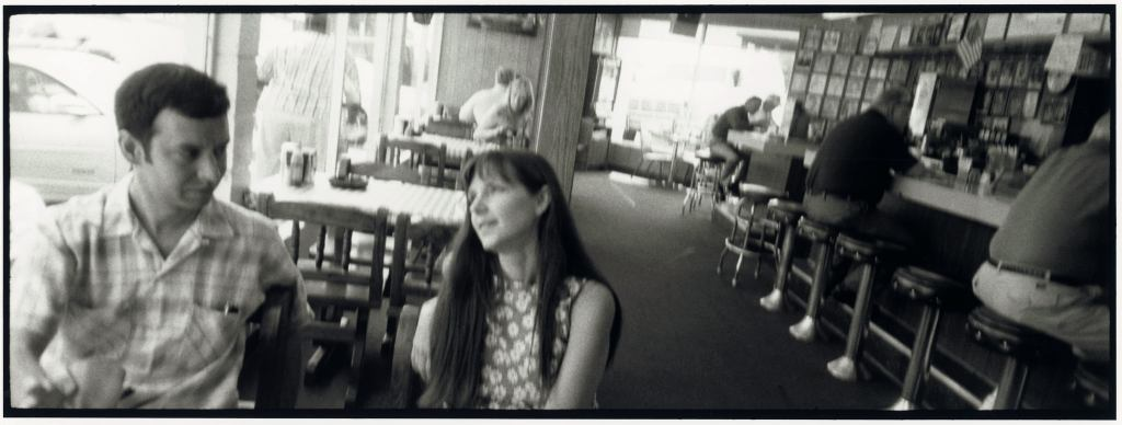 Bill Demain and Molly Felder, members of Swan Dive, sit in a diner. The photo is black and white.