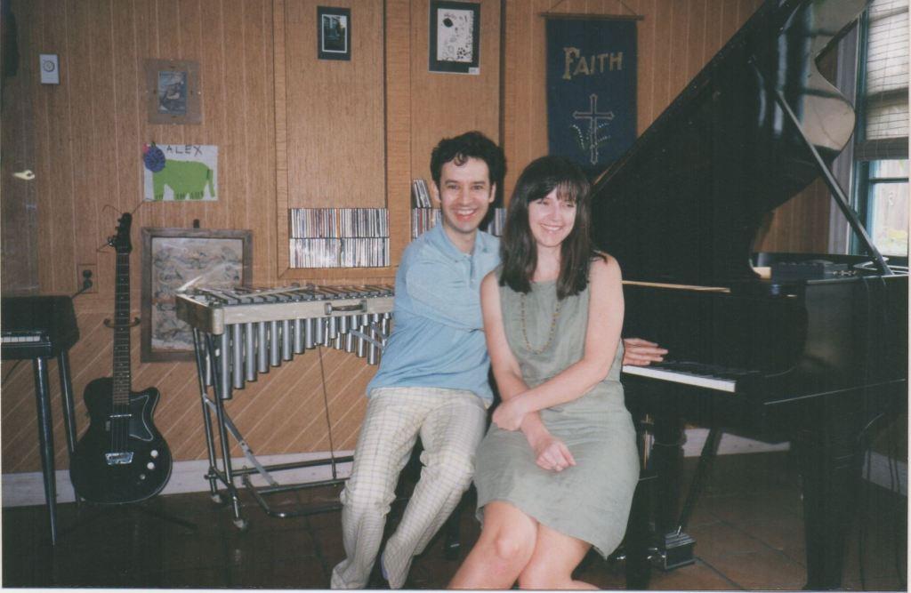 Bill DeMain and Molly Felder sit at a grand piano, smiling towards the camera.